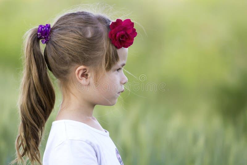 Profilera ståenden av den gulliga lilla allvarliga flickan i den vita T-tröja med den långa blonda ponny-svansen och den röda ros arkivbilder