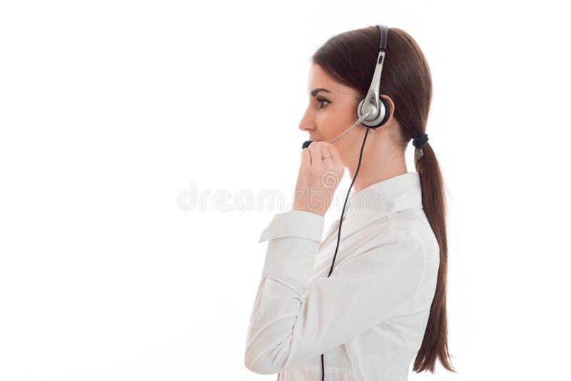 Profilera ståenden av den nätta unga kvinnan för arbetaren för brunettappellkontoret med hörlurar och mikrofonen som isoleras på  royaltyfri fotografi