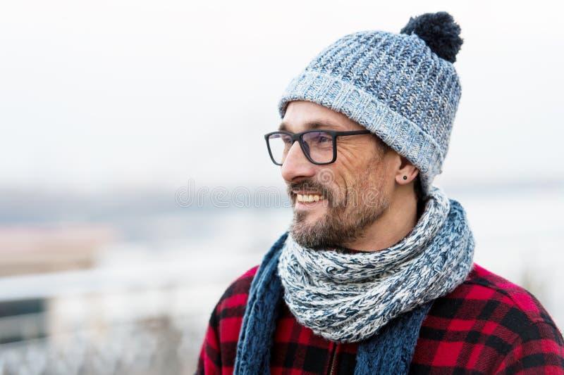 Profilera ståenden av den unga le mannen i rött omslag Vinter stucken kläder för stads- man Profil av den lyckliga skäggiga grabb arkivbild