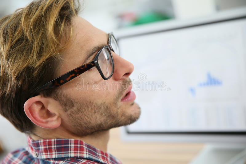 Profilera ståenden av den unga mannen på den skrivbords- datoren royaltyfri foto