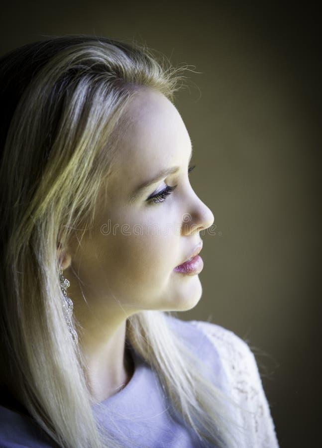 Profilera ståenden av den ursnygga blonda damen som är borttappad i tanke royaltyfria foton