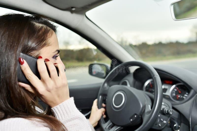 Profilera ståenden av en kvinna som kör en utsmyckad bil och talar på telefonen royaltyfri fotografi