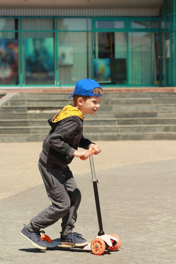 Profilera ståenden av en stilfull pojke i baseballmössa som rider en utomhus- sparkcykel arkivbilder