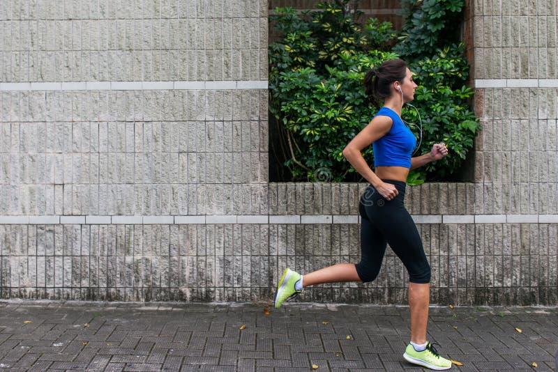Profilez la vue d'une jeune femme sportive établissant dehors Fille de forme physique courant sur le trottoir images libres de droits