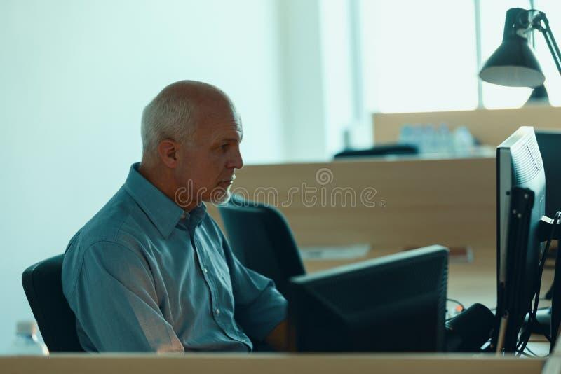 Profilez la vue de l'homme de senrio travaillant à l'ordinateur photo stock