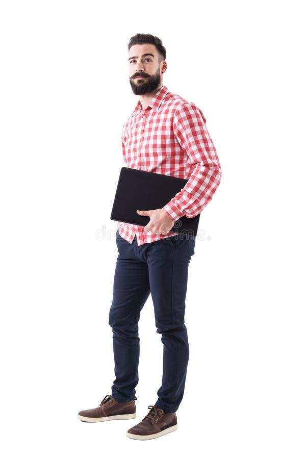 Profilez la vue de l'ordinateur portable de transport de jeune homme occasionnel futé barbu sous le bras regardant l'appareil-pho image stock