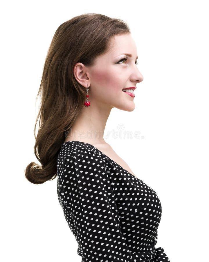Profilez le portrait de la jeune femme de sourire, d'isolement sur le blanc photos stock