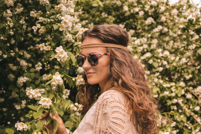 Profilez le portrait de la jeune femme hippie heureuse parmi des fleurs images stock