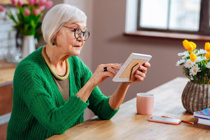 Profilfoto av den attraktiva äldre kvinnan som trycker på fotoet i ram arkivfoton