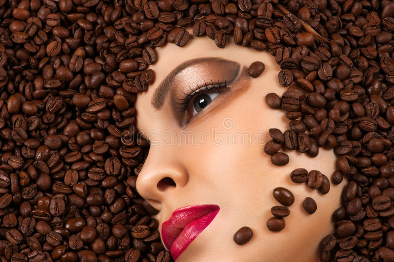 Profilfrauengesicht in den Kaffeebohnen stockfotos