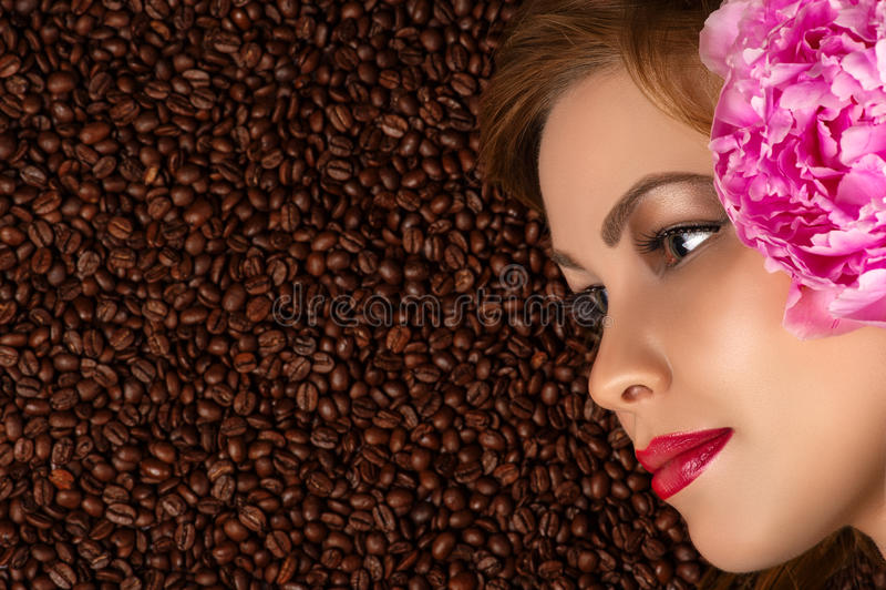 Profilgesicht mit Pfingstrose auf Kaffeebohnen stockfoto