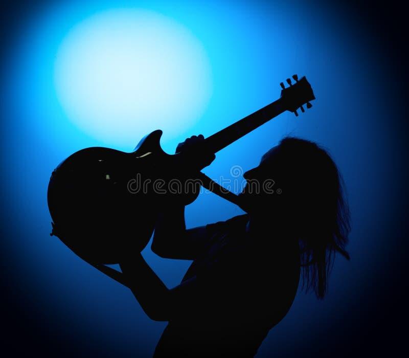 Profili i chitarristi di una banda rock con la chitarra su fondo blu fotografie stock libere da diritti