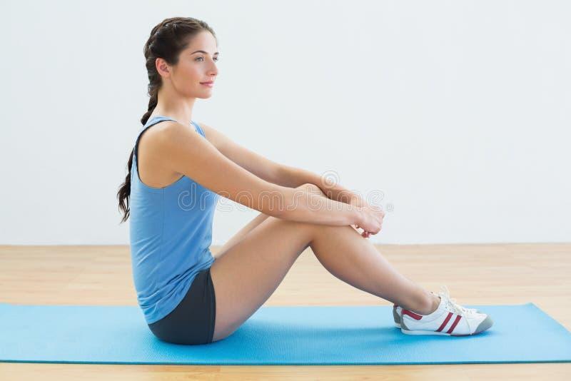 Profili il colpo di una donna di misura che si siede verticalmente sulla stuoia di esercizio immagine stock