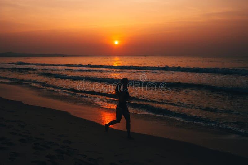Profili il giovane corridore femminile, corrente al tramonto sul mare fotografia stock