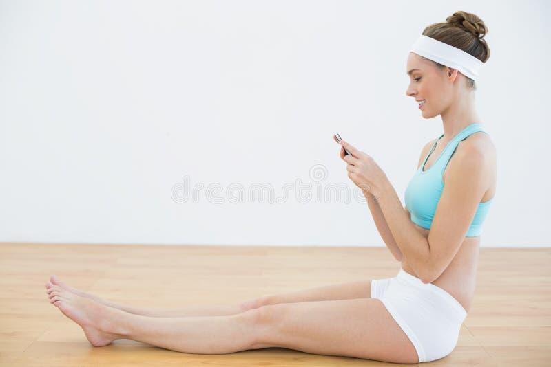 Profili il punto di vista della donna sportiva concentrata che per mezzo del suo smartphone immagini stock libere da diritti