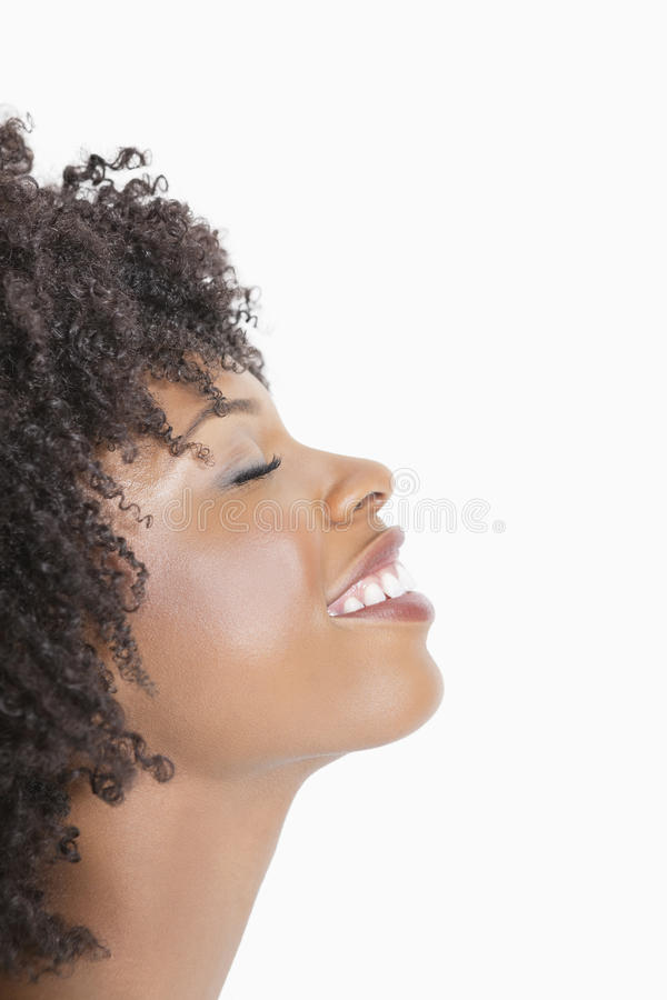 Profili il punto di vista di una donna afroamericana che sorride con gli occhi chiusi contro fondo grigio fotografia stock