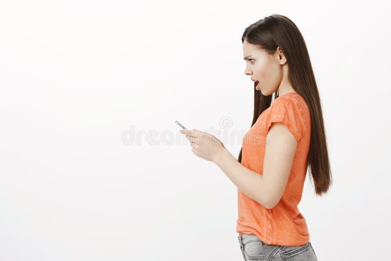 Profili il ritratto della donna caucasica espressiva sgomento colpita in maglietta arancio, tenente lo smartphone e fissante con immagini stock libere da diritti