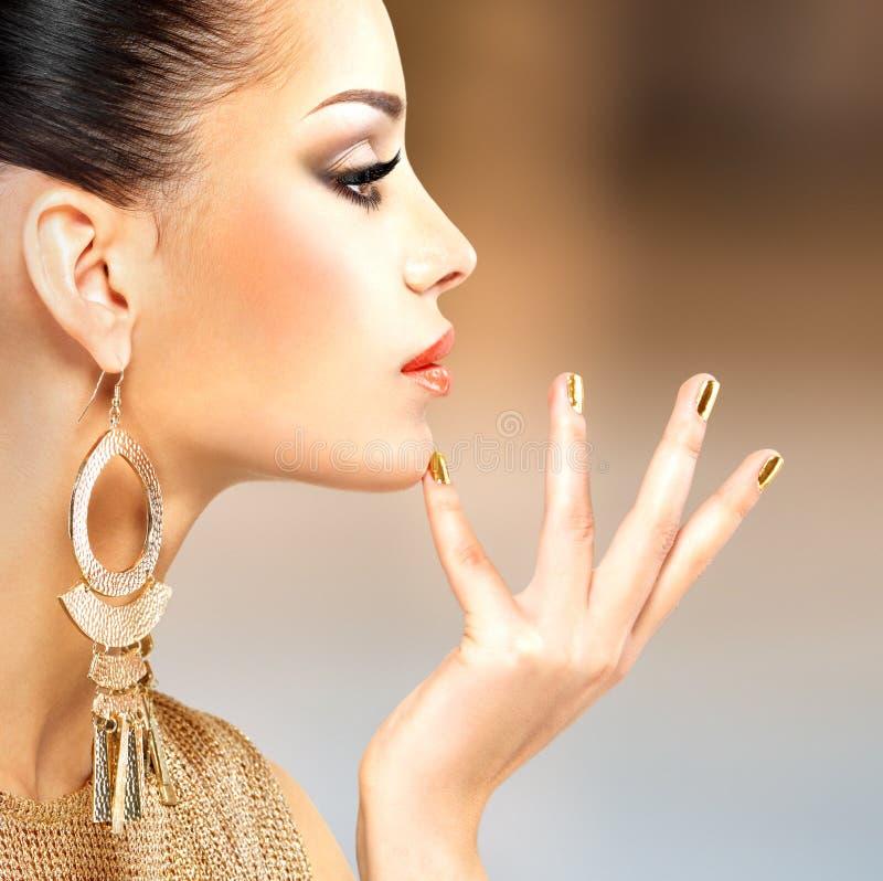 Profili il ritratto della donna di modo con bella mani dorata fotografie stock