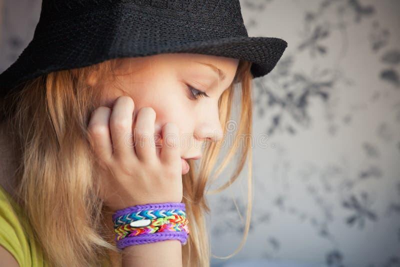 Profili il ritratto di bello adolescente biondo in black hat immagine stock