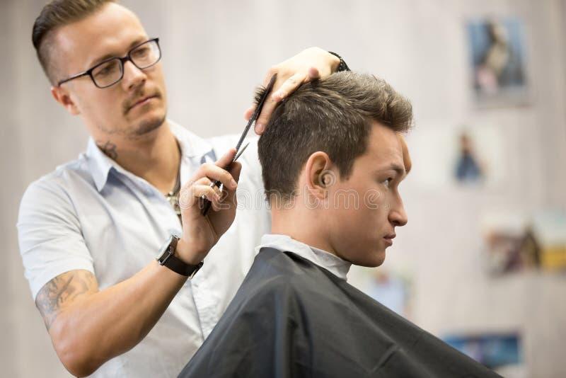 Profili il ritratto di vista del giovane attraente che ottiene il taglio di capelli immagini stock
