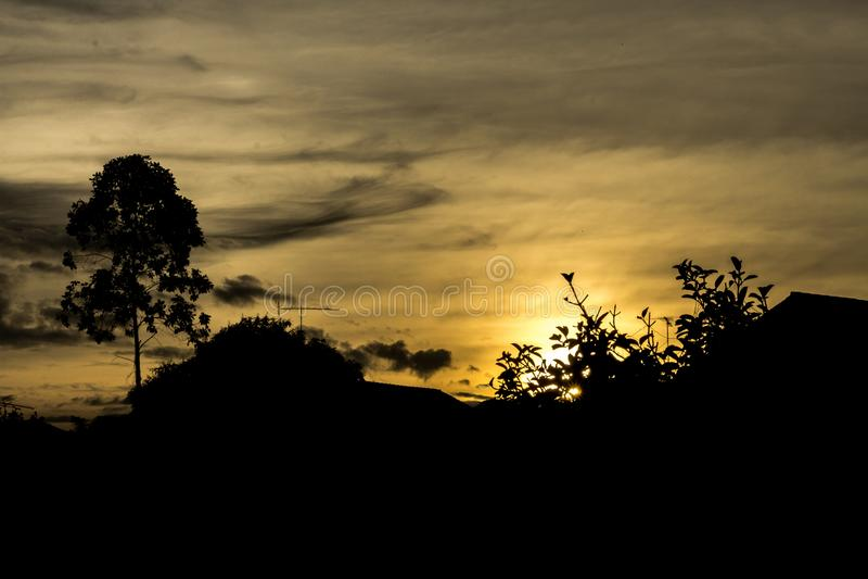 Profili l'immagine della casa del tetto e dell'albero con l'alba e il eveni fotografia stock