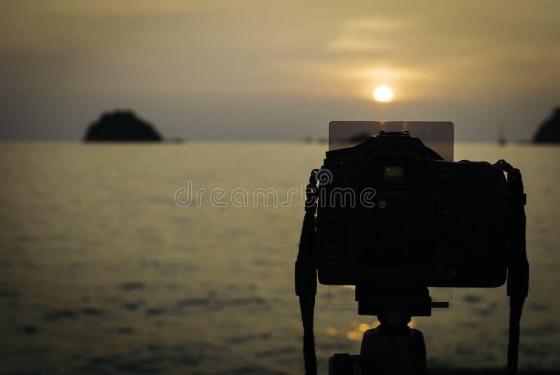 Profili l'immagine della macchina fotografica digitale sul treppiede durante il tramonto fotografia stock libera da diritti