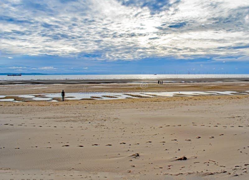 Profili la figura che affronta l'orizzonte del generatore eolico alla spiaggia di Crosby, Inghilterra immagine stock