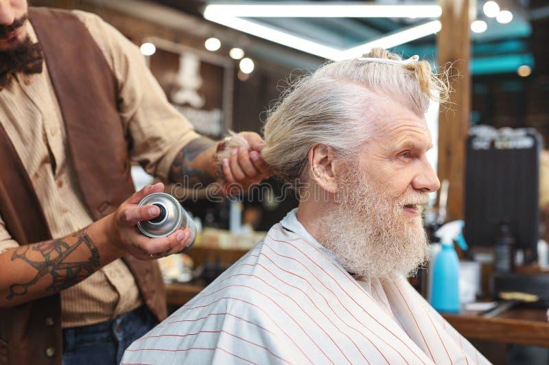 Profili la foto dell'uomo piacevole quella seduta nel parrucchiere fotografia stock