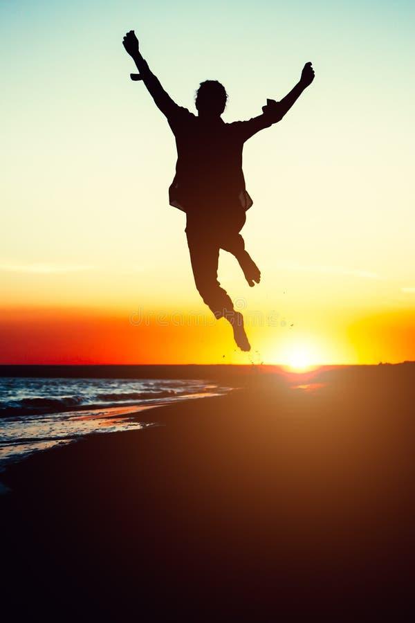 Profili la giovane donna che salta con le mani su sulla spiaggia al fotografie stock libere da diritti