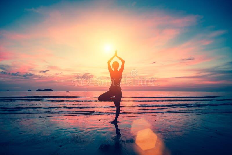 Profili la ragazza di yoga sui precedenti del mare sbalorditivo e del tramonto immagini stock