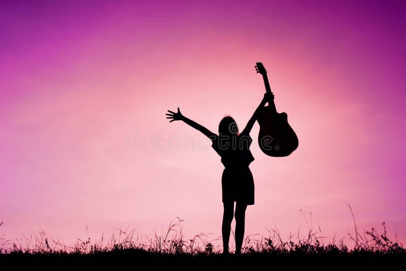 Profili la ragazza felice che gioca la chitarra al tramonto del cielo, Ti felice immagini stock libere da diritti
