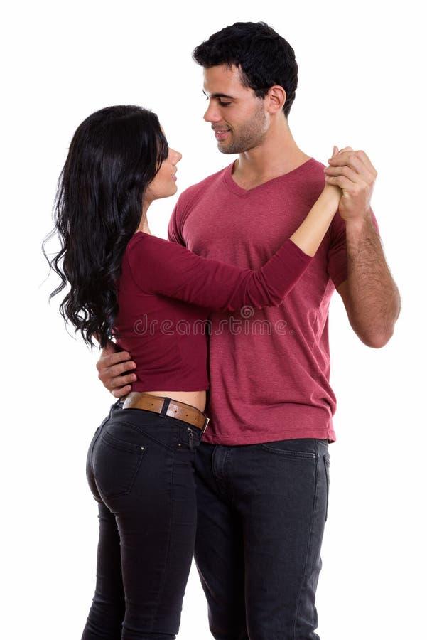 Profili la vista di giovani coppie felici che sorridono mentre ballano il togethe fotografia stock