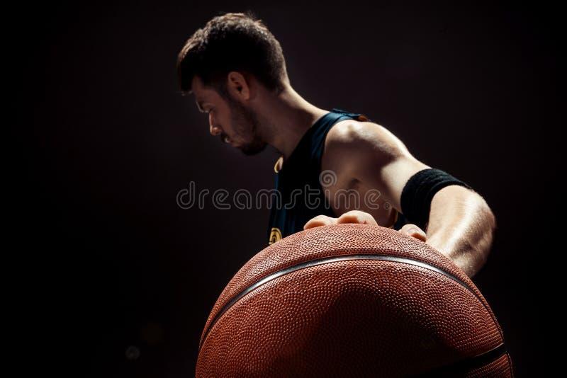 Profili la vista di una palla del canestro della tenuta del giocatore di pallacanestro su fondo nero immagini stock libere da diritti