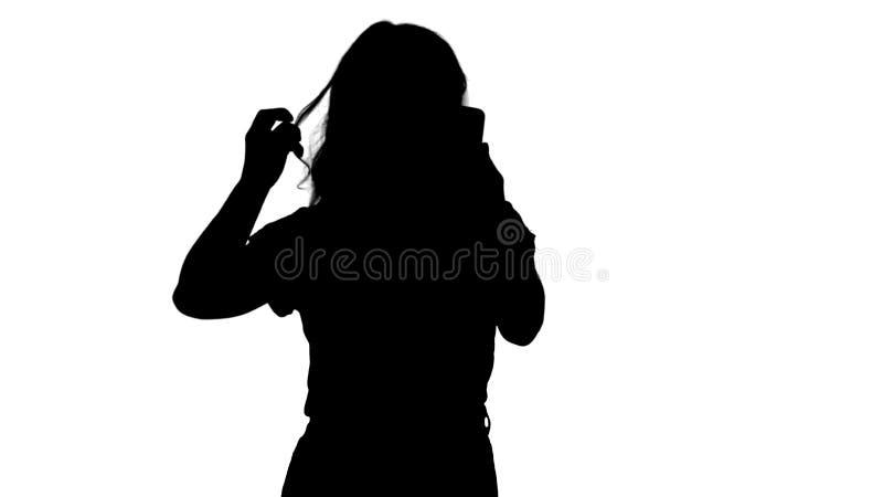 Profili una giovane donna piacevole raddrizza i suoi capelli che guardano nel cellulare royalty illustrazione gratis