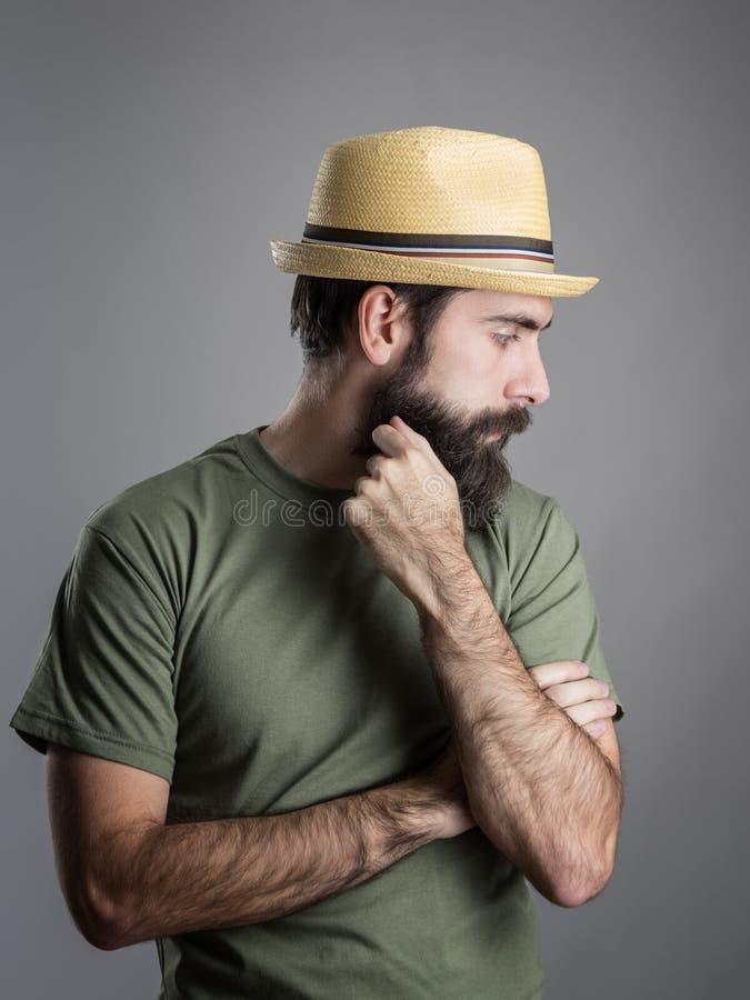Profilieren Sie Ansicht des tragenden Strohhutes des traurigen bärtigen Mannes, der weg schaut stockfotografie