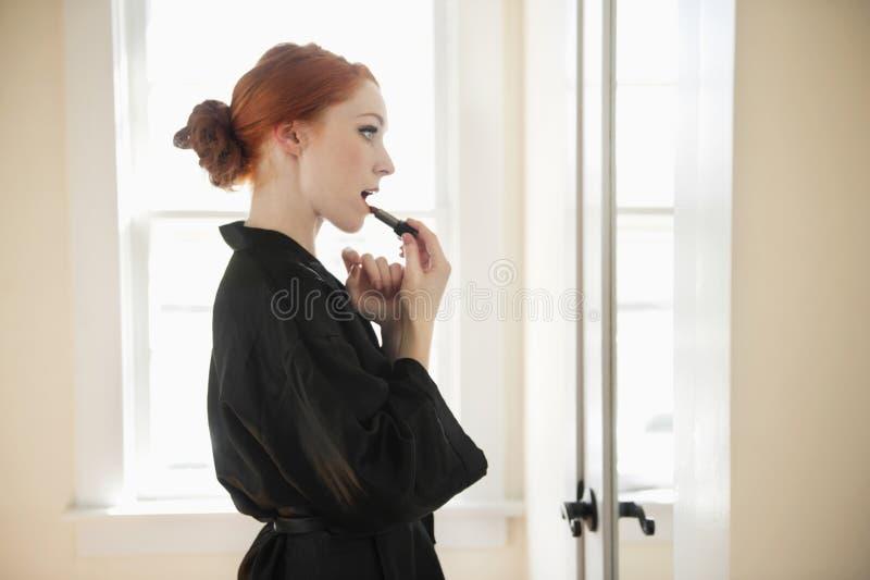 Profilieren Sie Ansicht einer jungen Frau in der Robe, die Lippenstift anwendet lizenzfreie stockbilder