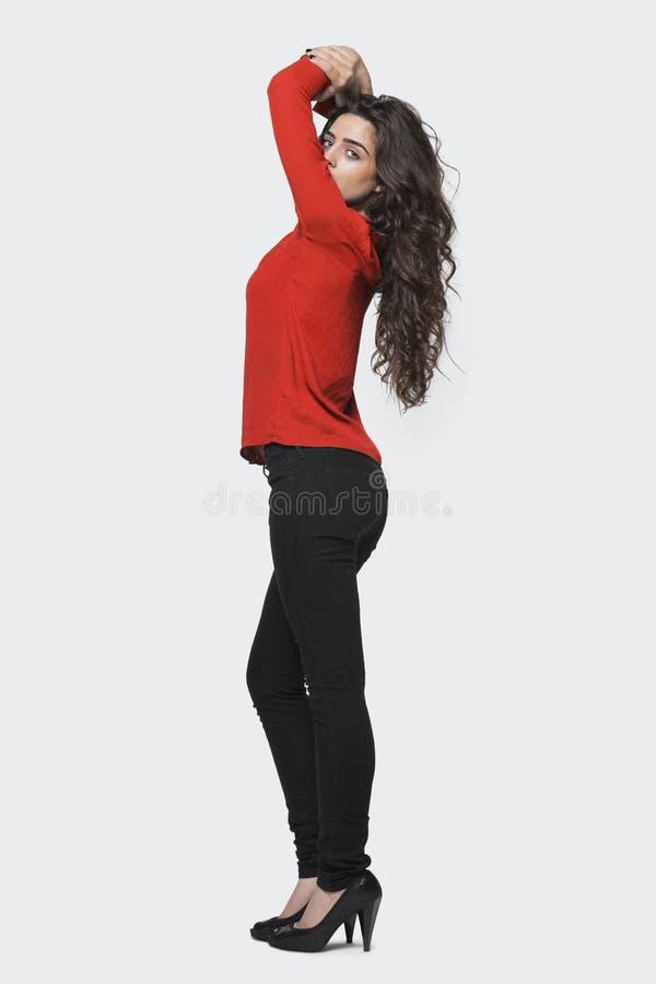 Profilieren Sie Ansicht einer jungen Frau, die über grauem Hintergrund steht lizenzfreie stockfotos