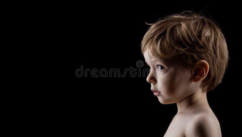 Profilieren Sie Porträt des vierjährlichen alten Jungen über Schwarzem lizenzfreie stockbilder
