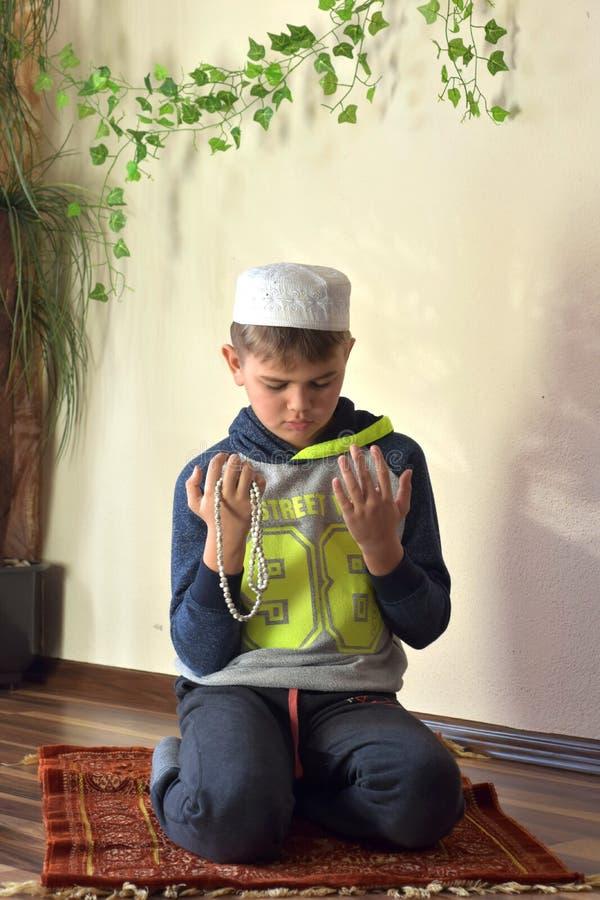Profilieren Sie Porträtbild des jungen netten moslemischen Jungen, der traditionelle islamische Gebetshutkappe trägt stockfoto