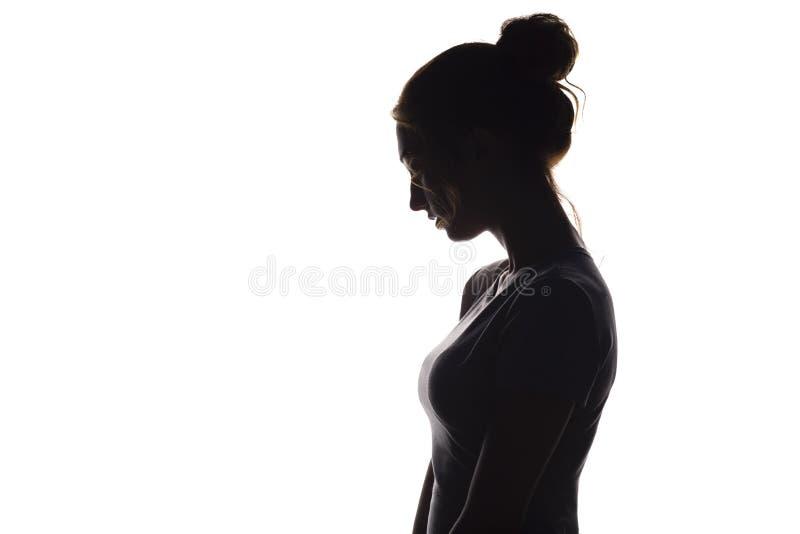 Profilkonturn av en eftertänksam flicka, en ung kvinna fällde ned hennes huvud ner på en vit isolerad bakgrund fotografering för bildbyråer