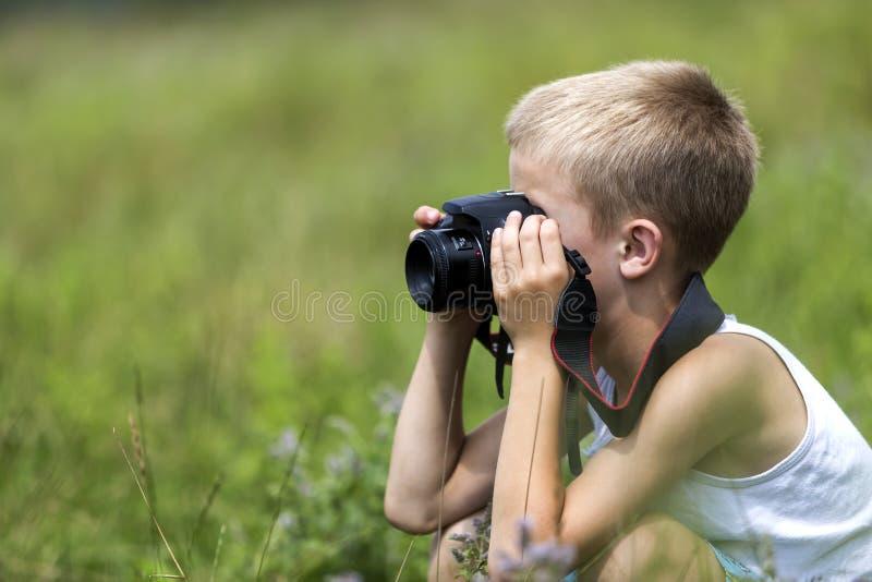 Profilnärbildstående av den unga blonda gulliga stiliga barnpojken med kameran som utomhus tar bilder på den ljusa soliga våren e royaltyfria bilder