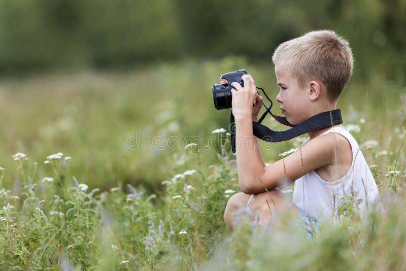 Profilnärbildstående av den unga blonda gulliga stiliga barnpojken med kameran som utomhus tar bilder på den ljusa soliga våren e fotografering för bildbyråer
