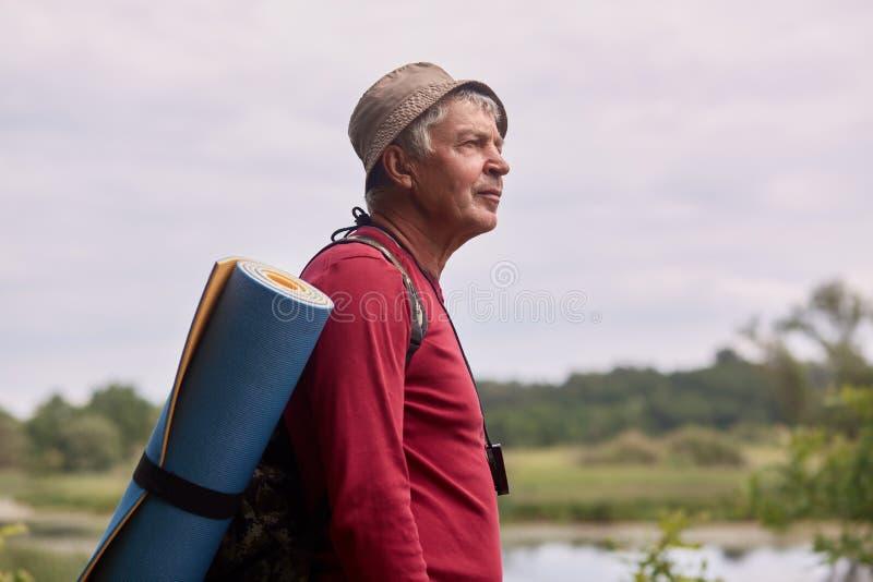 Profilo alto vicino sparato dell'uomo di eldery con lo zaino, il maglione casuale rosso d'uso ed il cappuccio, stando vicino al f fotografia stock libera da diritti