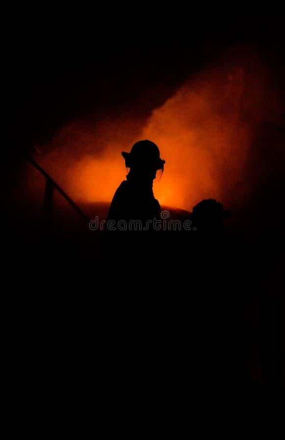 Profilo del pompiere contro fuoco immagine stock libera da diritti