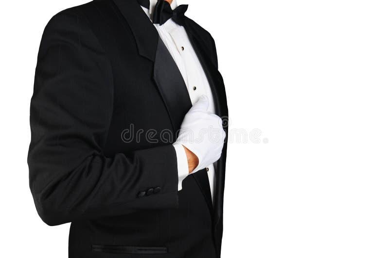 Profilo del primo piano di un uomo che indossa uno smoking ed i guanti bianchi che tengono il suo risvolto immagine stock libera da diritti