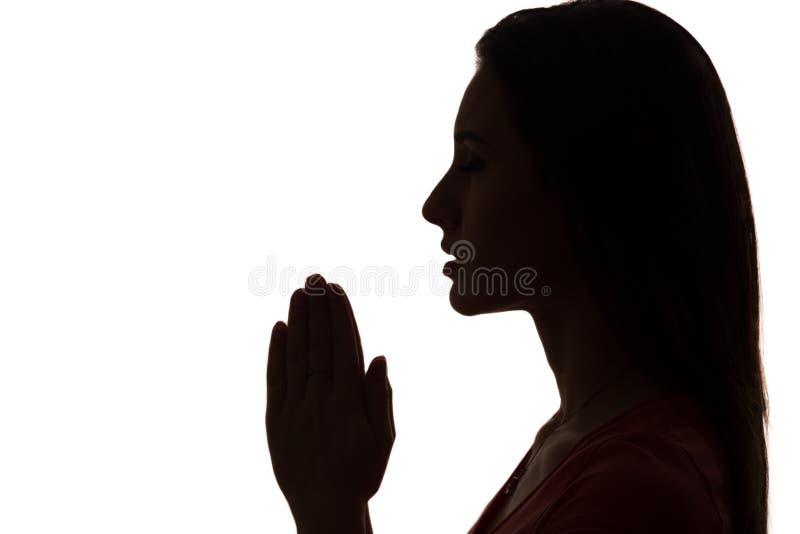 Profilo del primo piano di una donna che prega nella siluetta isolata immagine stock libera da diritti