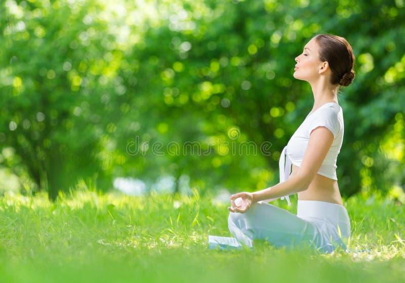 Profilo della donna allegra nel gesturing di zen di posizione di loto immagini stock libere da diritti