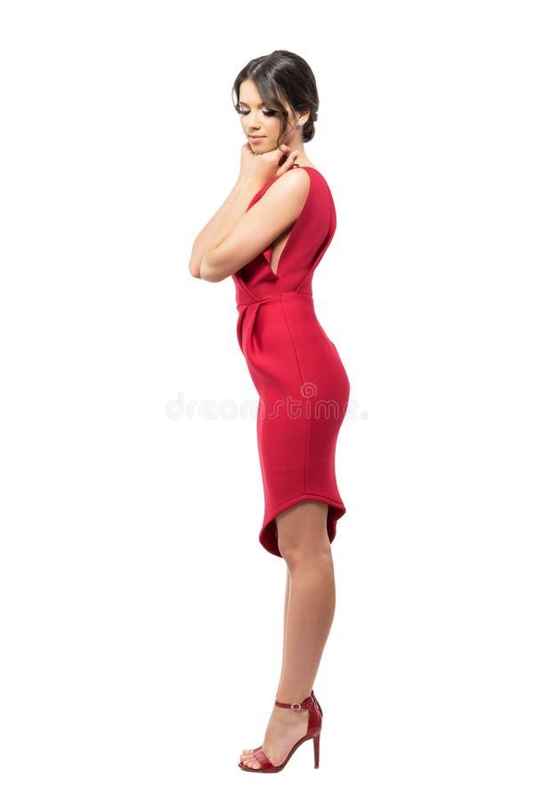 Profilo della donna femminile in vestito e tacchi alti rossi con le mani sul mento che guarda giù immagini stock