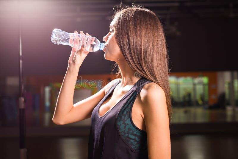 Profilo di bella donna che va bere una certa acqua dalla bottiglia di plastica dopo l'allenamento fotografie stock libere da diritti