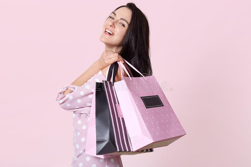 Profilo di bella giovane donna felice con capelli scuri lunghi, tenente i sacchetti della spesa sulla sua spalla ed esaminante co fotografie stock libere da diritti